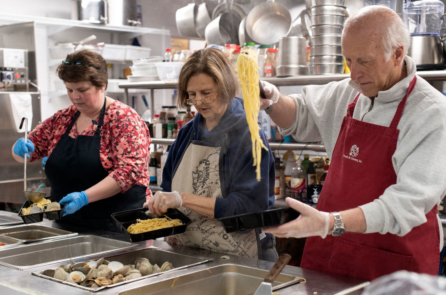 HYANNIS - Faith Family Kitchen volunteers George and Glenna Cappola and Donna Vashon serve up a true New England supper on Friday, April 3, 2020. A donation from SPAT featured Holbrook littlenecks over butter garlic pasta.