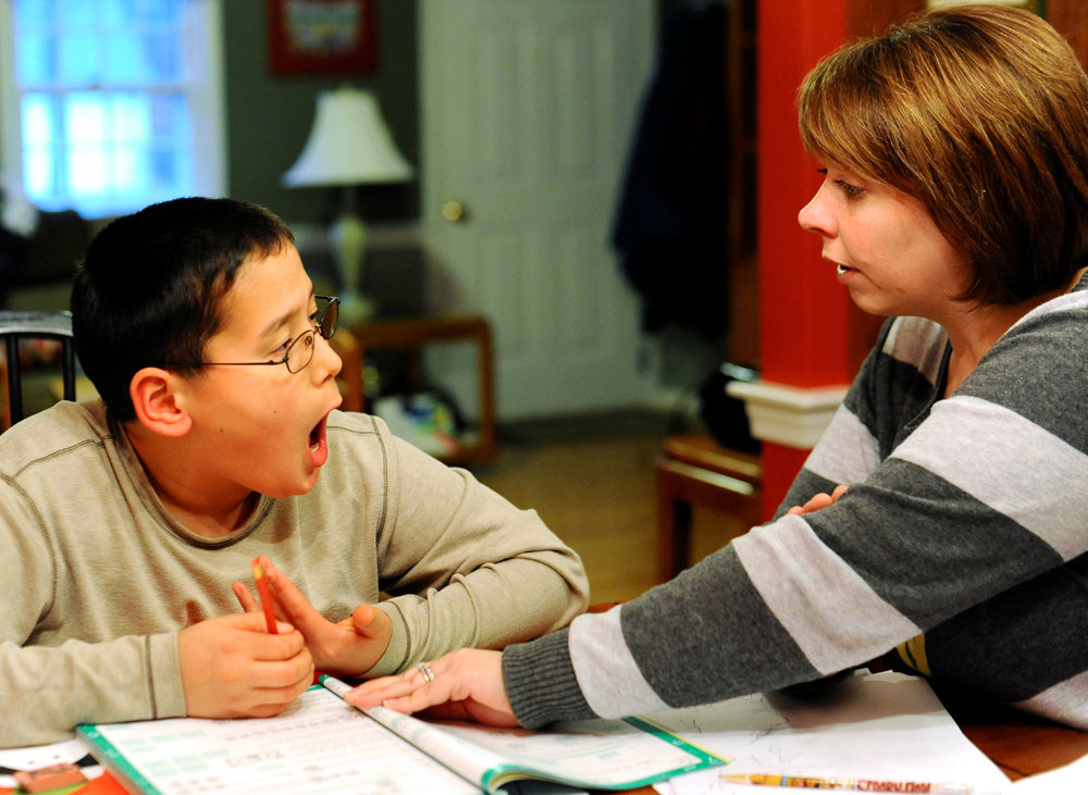 WEST YARMOUTH -- 03/31/11 -- Nickolas Qvarnstrom, 10, yells at his mother, Tina, when he becomes frustrated while correcting his subtraction homework. Math is one of Nickolas's least favorite subjects. He is currently learning at a second grade level.