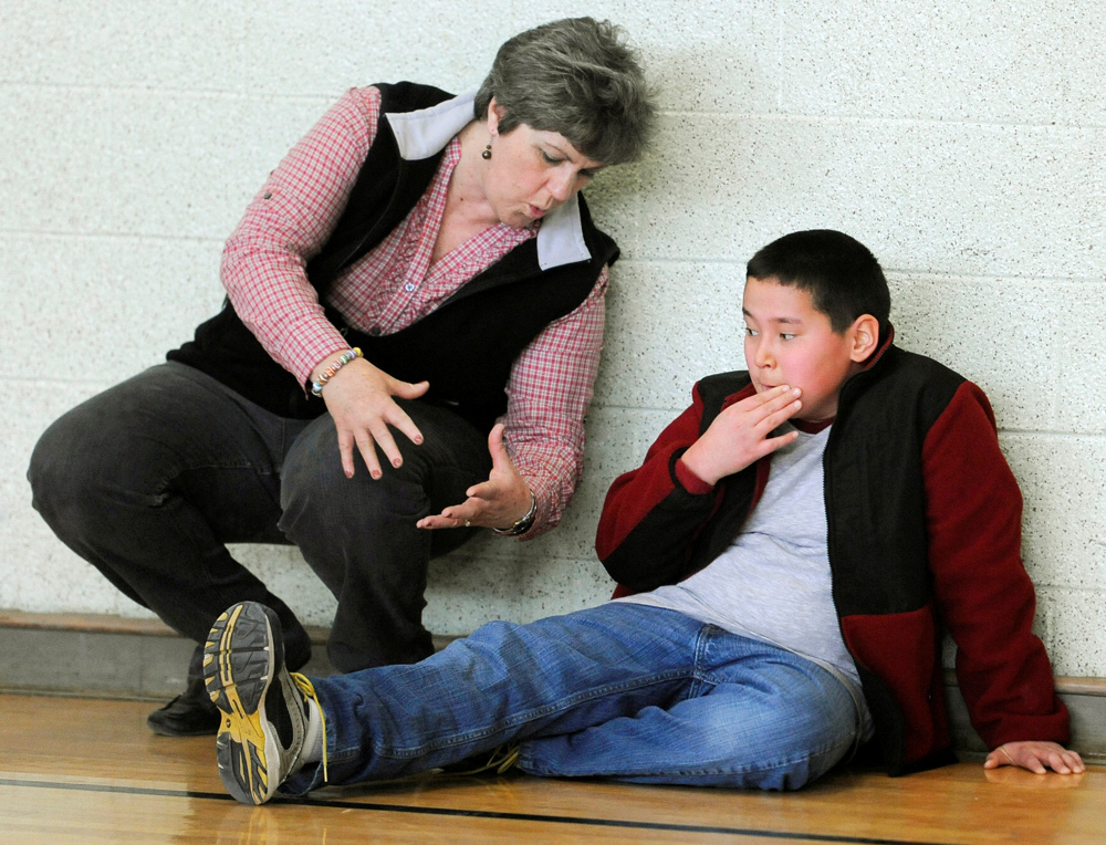 OSTERVILLE -- 03/30/11 -- Cape Cod Collaborative para professional Pat Rice Fraser calms down Nickolas Qvarnstrom, 10,  after he thought he broke his knee cap playing a game at recess. His mother, Tina Qvarnstrom, believes that Nick's extreme reaction is an example of his anxiety and obsessive compulsive disorder.