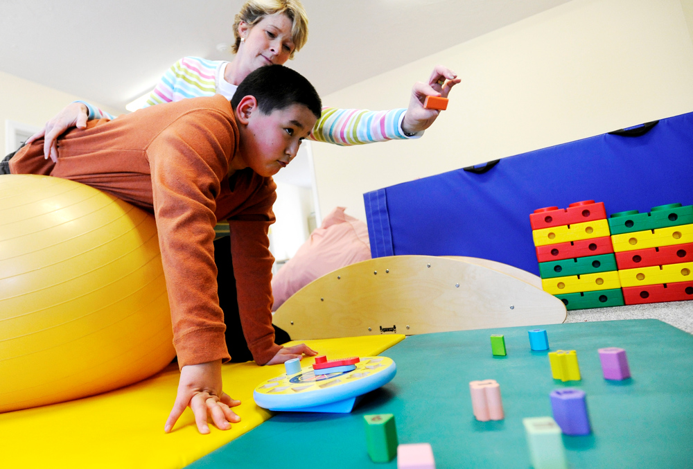 MASHPEE -- 03/28/11 -- Nickolas Qvarnstrom, 10, performs an upper body strength, coordination and balance exercise with his occupational therapist Madeline Langley at Cape Kids Therapy and Sensory Center.
