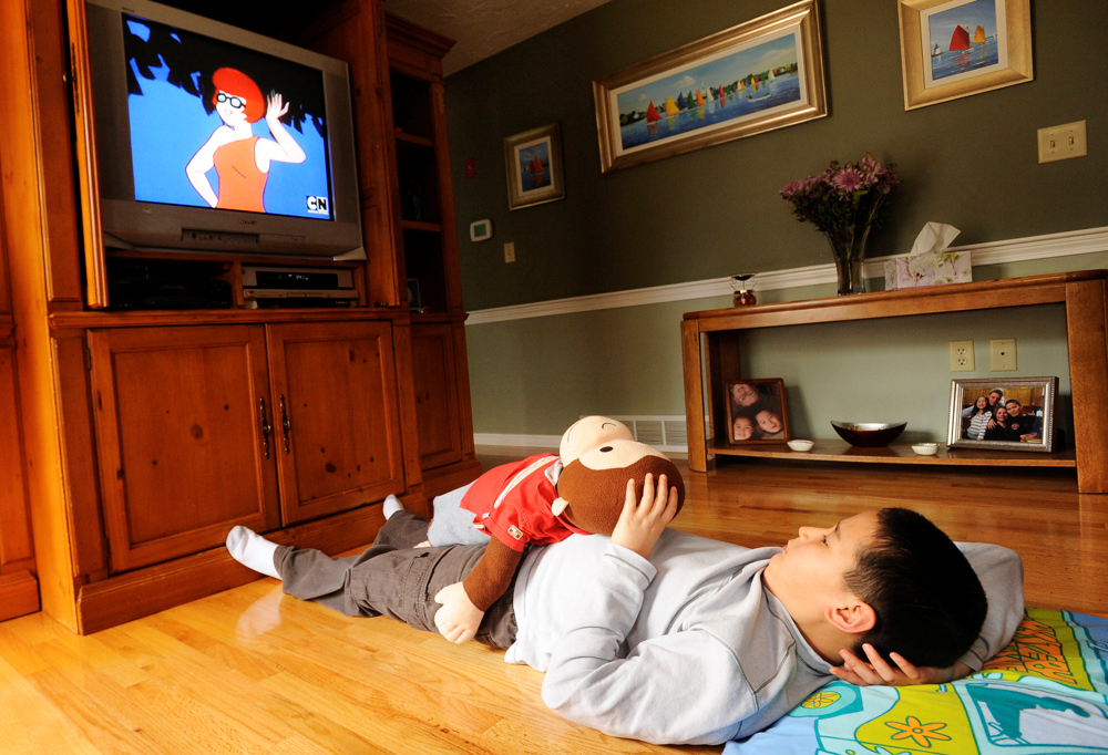 WEST YARMOUTH -- 03/24/11 -- Nickolas Qvarnstrom, 10, watches Scooby Doo with his favorite monkey after school. The monkey is dressed in the clothes Nickolas was wearing when his mother adopted him from an orphanage in Kazakhstan at 3 years old.