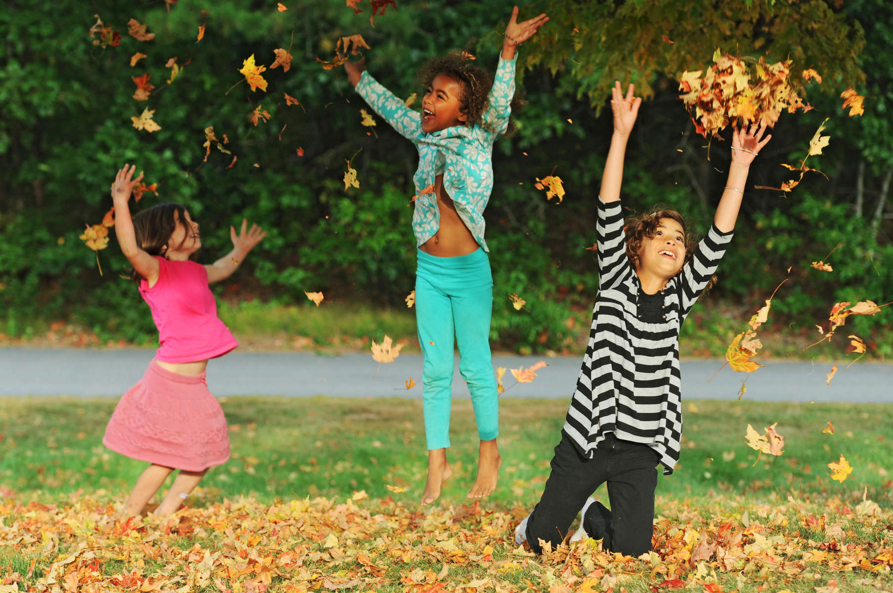 From left, Layla Vickers, 5, Amalia Thompson, 5, and Olivia Thompson, 8, all of West Barnstable blissfully toss leaves in the air in front of West Barnstable Elementary School on the second day of autumn.
