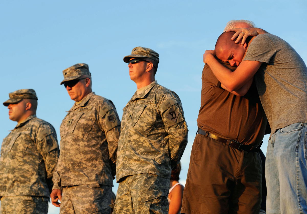 Danny Gallagher, 21, brother to Cpl. Matthew Gallagher, is comforted by his father, Peter Gallagher, during the candlelight vigil at Old Silver Beach on Wednesday, June 29, 2011.