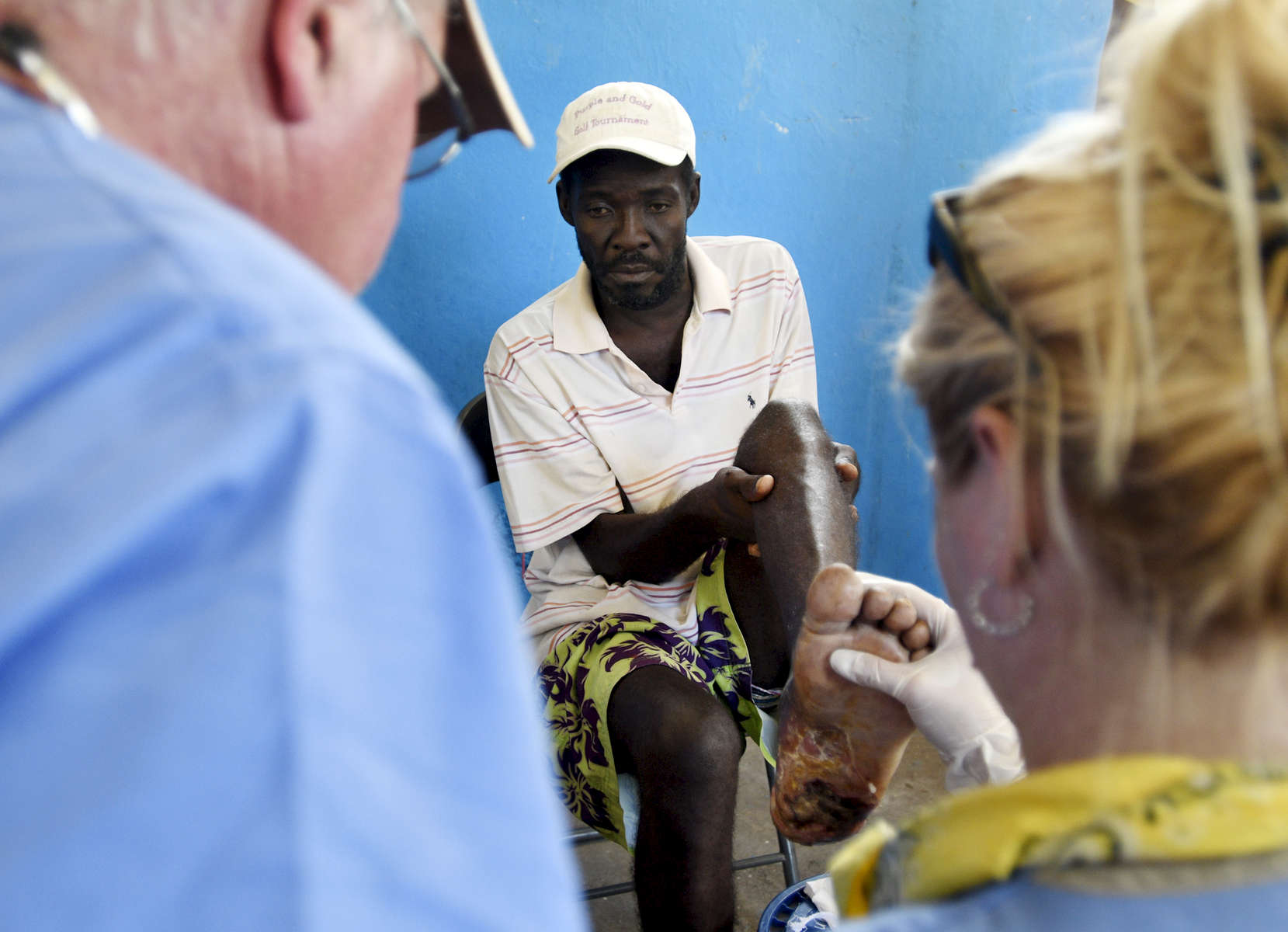Roger Juno, 46, shows his infected wound to Dr. John Harrington and RN Donna Muse-Maynard at the Adventist Church in Ducis, Haiti on Wednesday, November 2, 2016. He stepped on a lightbulb in the commotion of Hurricane Matthew.