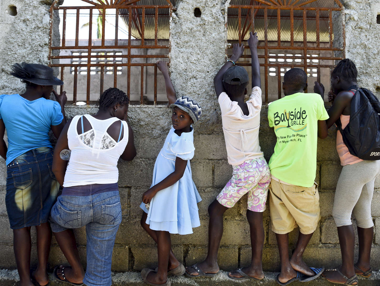 Children and adults peer through the windows of the Adventist Church waiting to be admitted to the Forward in Health clinic in Ducis, Haiti on Wednesday, November 2, 2016.