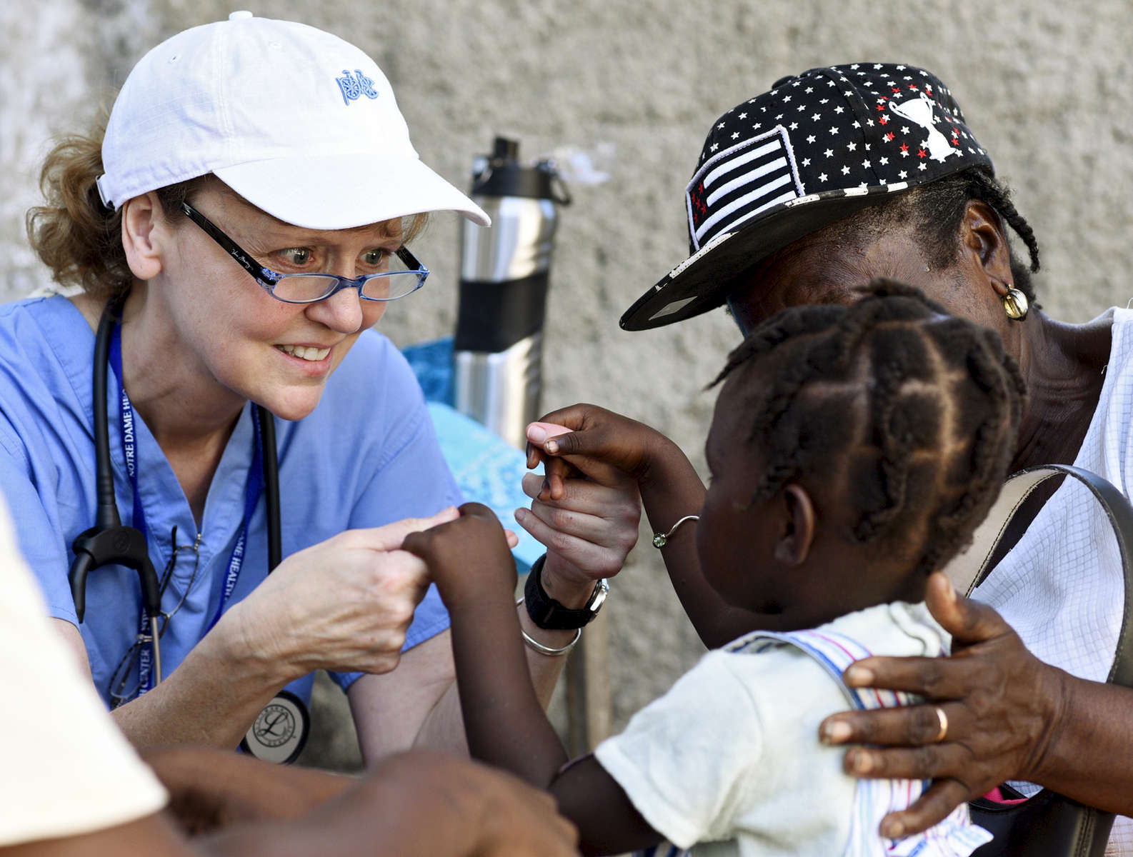 Forward in Health trip leader Paula Mulqueen evaluates a toddler at the Adventist Church in Ducis, Haiti on Wednesday, November 2, 2016.
