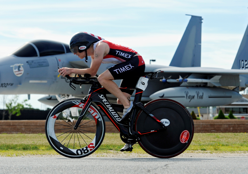 Craig Mitchell, 24, of Abington zooms past the 102nd Intelligence Wing retired F-15 Eagle jet outside the gates of Otis Air National Guard base during the Hero Triathlon on Sunday, June 22, 2014.