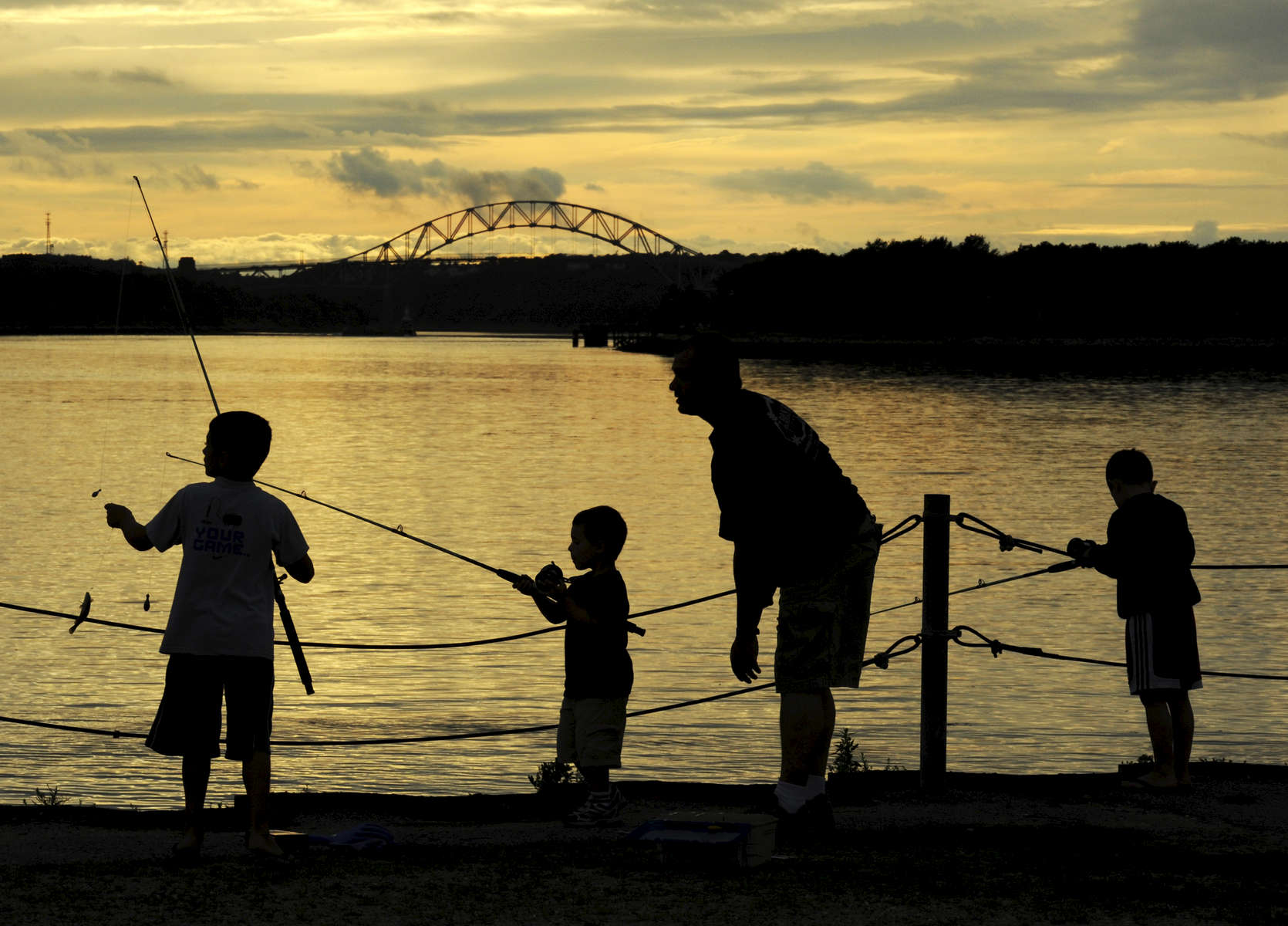 SANDWICH -- 081611 -- From left, Alex Leoni, 9, pulls up a little fish with Joe Lascola, 4, Michael Leoni and Michael Leoni, 6, at the Cape Cod Canal on Tuesday evening. The foursome of Newton and Sandwich is keeping up with an occasional ritual of having dinner at Seafood Sams and then casting out on to the Canal using hotdog pieces for bait.  Cape Cod Times/Christine Hochkeppel 081611ch06