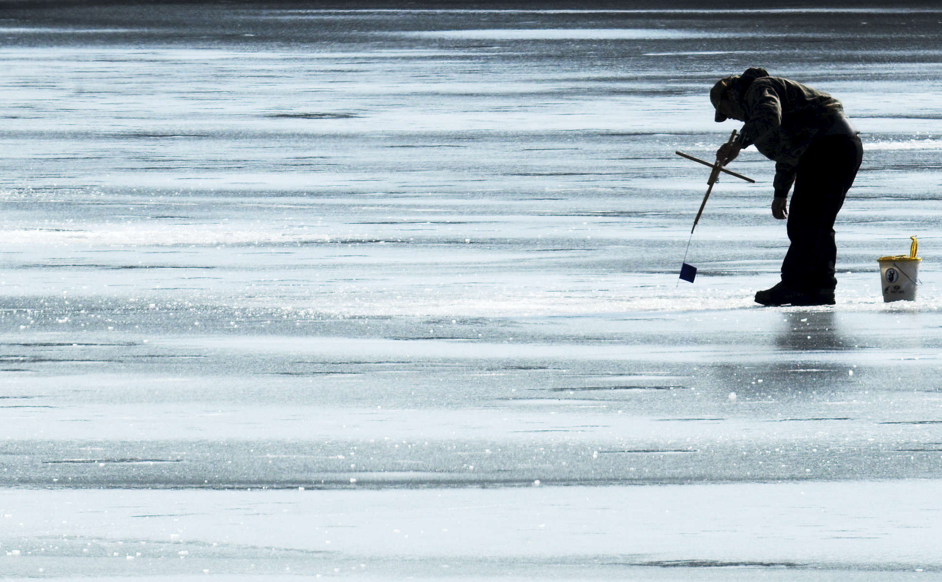 YARMOUTH PORT -- 01/23/11 -- Matthew St. Thomas of Sterling checks one of his tilts in the hopes of discovering a perch or bass on the line at Dennis Pond on Sunday morning. {quote}As soon as there's ice, we're here,{quote} he said of how often he and his crew come to the Cape. {quote}There's less snow and better fishing.{quote} 012311ch02 Cape Cod Times/Christine Hochkeppel