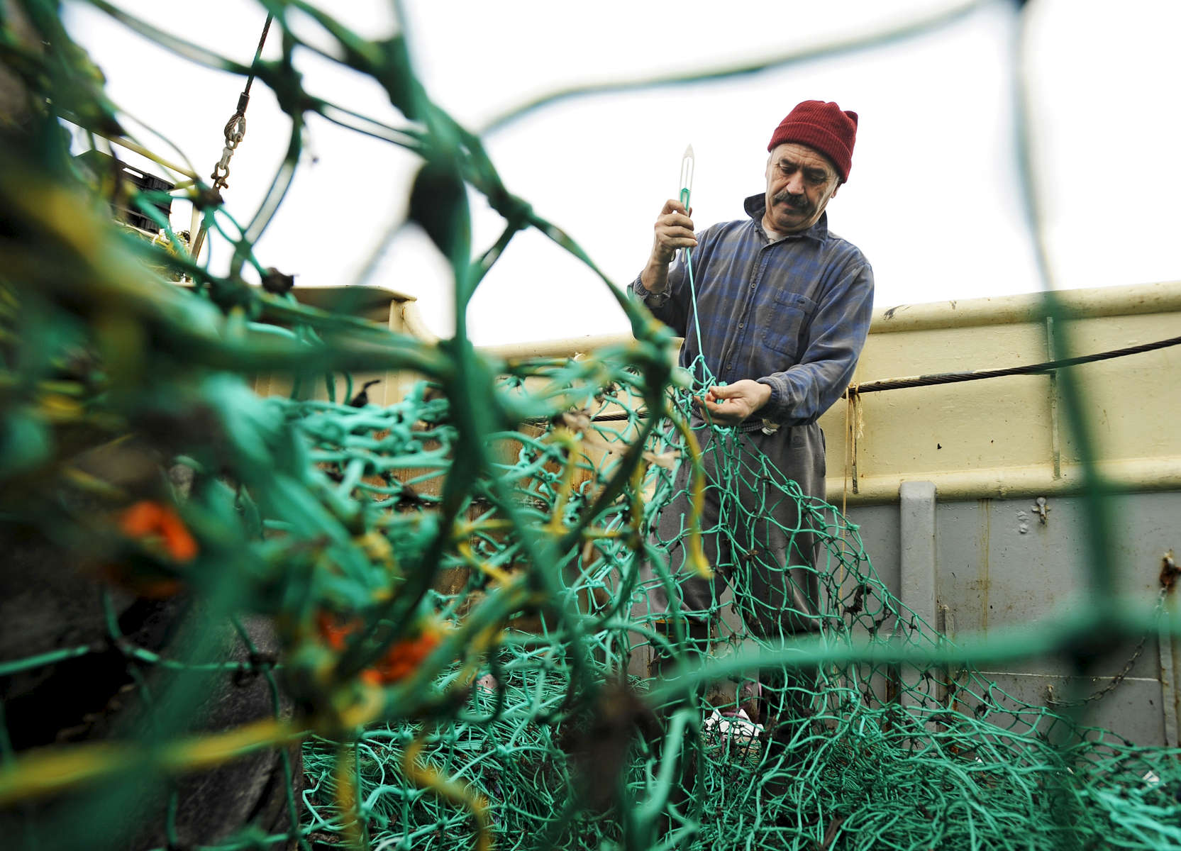 PROVINCETOWN -- 03/23/11 -- New Bedford fisherman Alfred Conde, 61, repairs an 80 by 50 foot section of net aboard 75-foot dragger Lady Patricia docked at MacMillan Pier. The crew's brand new net became all chewed up when it got caught in the mud as they fished for haddock, cod, pollock and sole.Cape Cod Times/Christine Hochkeppel 032311ch05