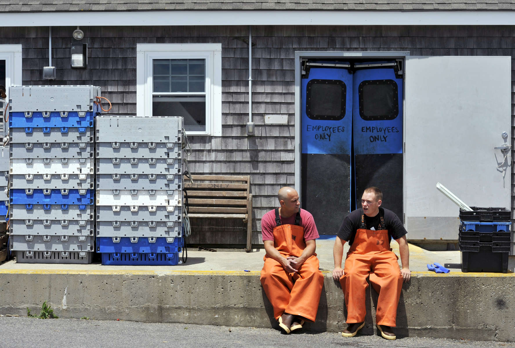 CHATHAM -- 062712 -- From left, onshore processors Mario Botelhofilho of South Yarmouth and Jared Taylor of Chatham catch a little sun while they chat on a break from culling catch at the Chatham Fish Pier.  Cape Cod Times/Christine Hochkeppel