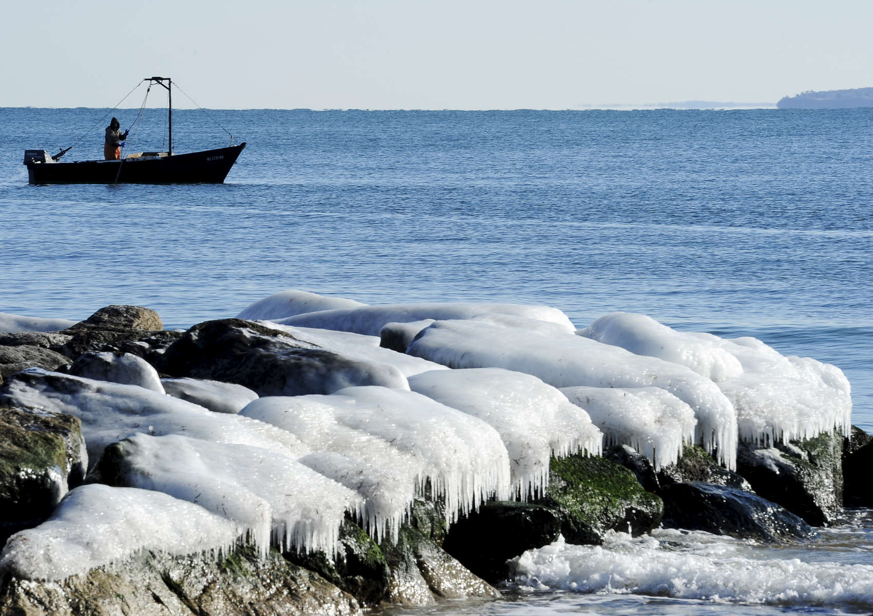 FALMOUTH -- 010914 -- A fisherman hauls up his catch near an ice-coated jetty off Surf Drive on Vineyard Sound.   Christine Hochkeppel/Cape Cod Times