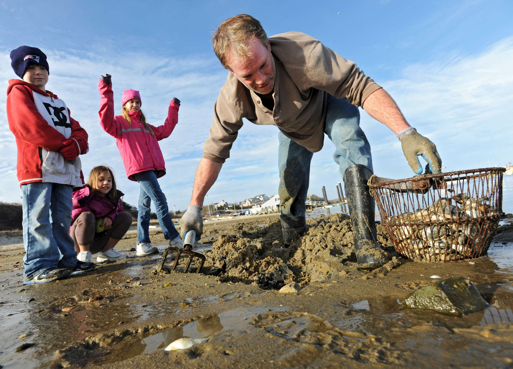 CHATHAM -- 120511 -- Commercial fisherman Chris Fontaine of Chatham digs up steamers for dinner with his daughters Christiana, 10, center, and Rabecca Fontaine, 9, and stepson Maddy White, 9, left, near the Fish Pier. The kids were able to accompany Chris on his clamming expedition because they had a half day of school. Chris was trying to fill a bushel basket before taking Maddy to his yoga class. For this family of seven, planning meals can be a challenge. He and his wife will enjoy the steamers but the kids don't have the palate for shellfish. They said they are voting to decide between tacos and burgers.  Cape Cod Times/Christine Hochkeppel 120511ch01