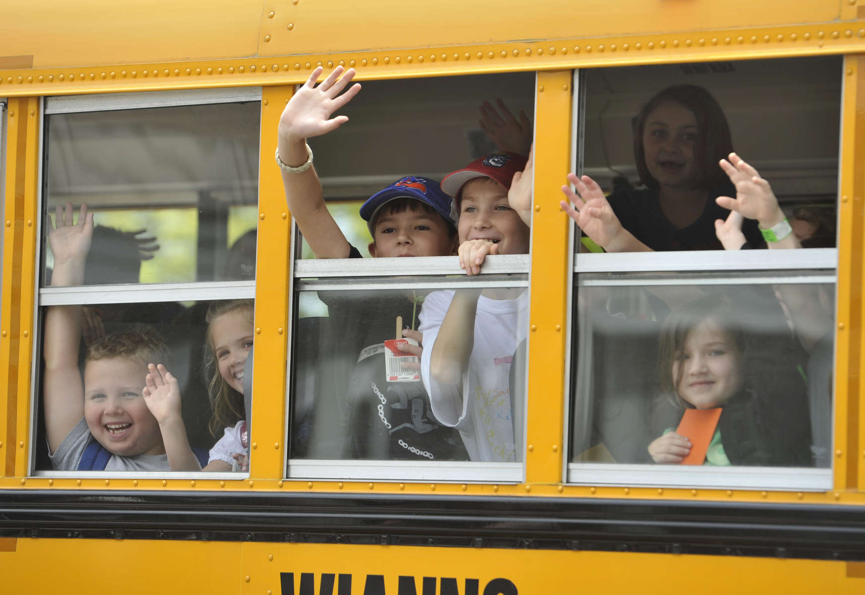 West Villages Elementary School students wave to their teachers as their bus pulls away on the last day of school.