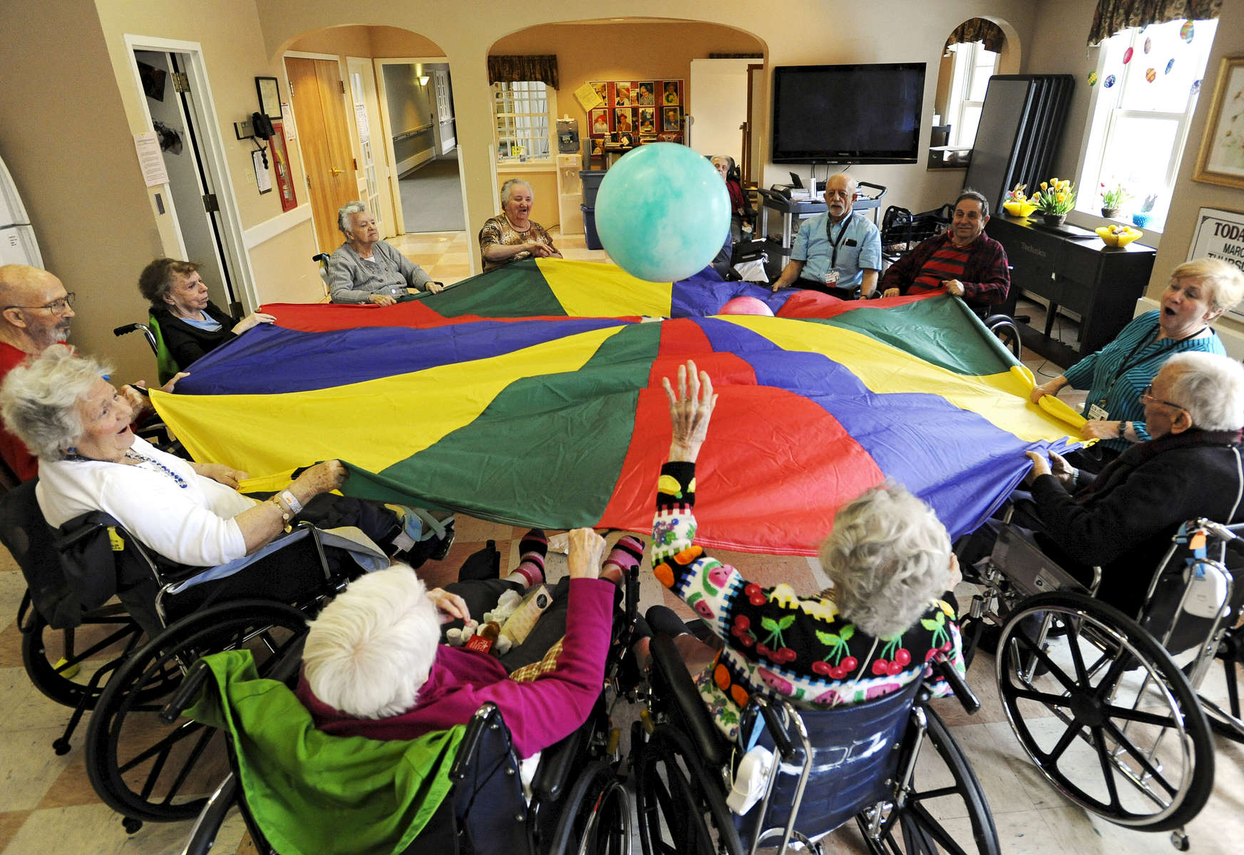 Dee Lawrence and Margaret O'Hara swat at the ball during therapeutic exercise session with the parachute at the JML Care Center. Federal cuts to Medicare reimbursement rates will impact nursing home facilities on the Cape.