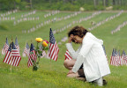 Sheryl Satterthwaite kneels at the grave of her husband, Army Spc. Dennis Satterthwaite, who served during Desert Storm, on Memorial Day at Massachusetts National Cemetery in Bourne, Mass.