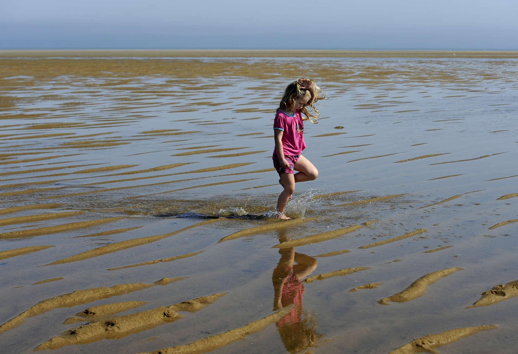 Kate Bassett, 5, of Brewster gets her feet wet at Point of Rocks Beach on Sunday.