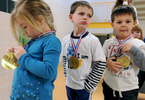 From left, Payten Rogovich, 4, Tyler Layton, 4, and Landon Miller, 3, sport their gold medals after the pre-K Olympics in the Harwich Elementary School gymnasium.
