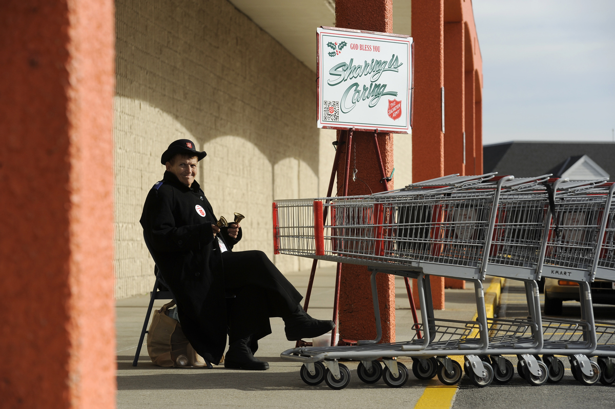 Judy Underwood, 72, of Hyannis rings her bells soliciting donations to the Salvation Army as a K-Mart employee pushes carts into the store. She has volunteered as a ringer for over 50 years.