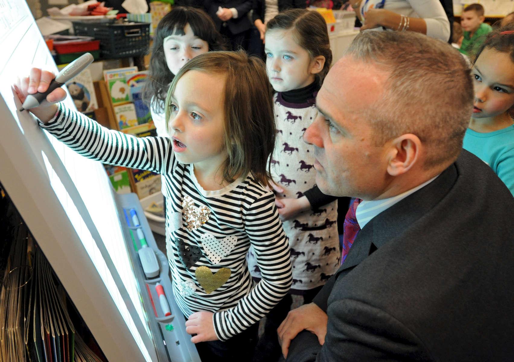Secretary of Education Matthew Malone watches kindergartner Chloe Bridges use a smart board at Kenneth C. Coombs Elementary School.