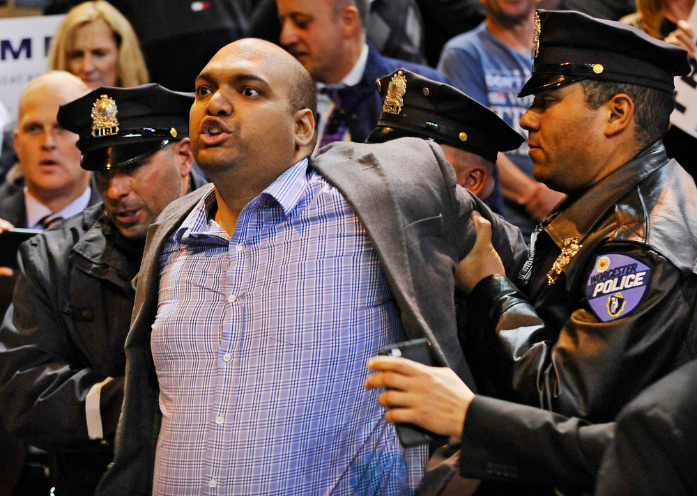 Peter Rondon, 29, of Worcester yells {quote}Trump is a racist{quote} as he escorted out by police at Republican presidential candidate Donald Trump's rally at the DCU Center on Wednesday, Nov. 18, 2015.