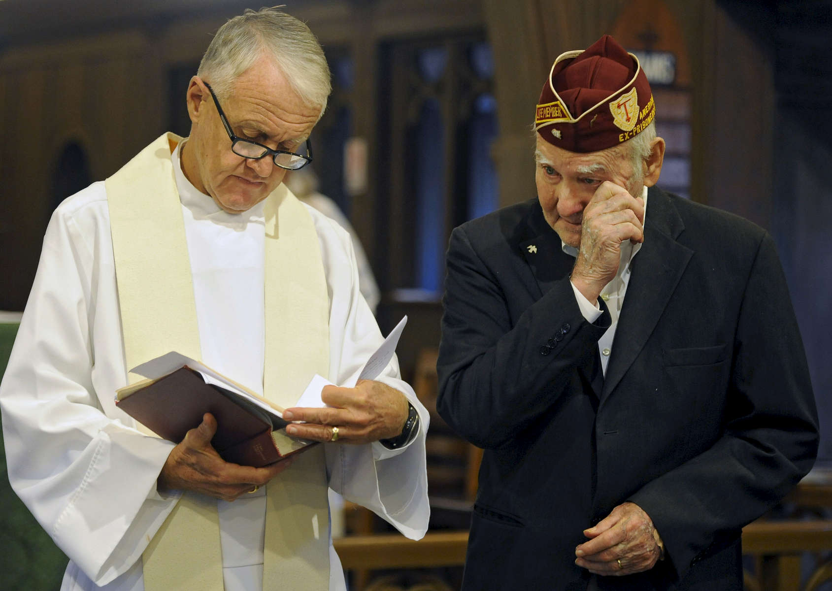 Rev. Mark Anschutz reads while Carroll {quote}Pete{quote} Gouger, 92, of South Yarmouth, who is an Air Force veteran of World War II and was a POW, wipes away a tear at the beginning of the Veterans Day Service of Remembrance at St. Mary's Episcopal Church.
