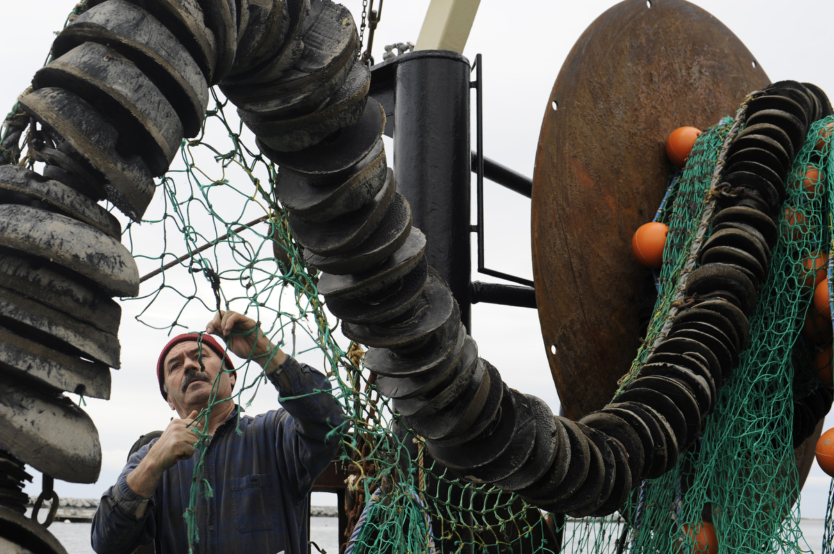 New Bedford fisherman Alfred Conde, 61, repairs an 80 by 50 foot section of net aboard 75-foot dragger Lady Patricia docked at MacMillan Pier. The crew's brand new net became all chewed up when it got caught in the mud as they fished for haddock, cod, pollock and sole.