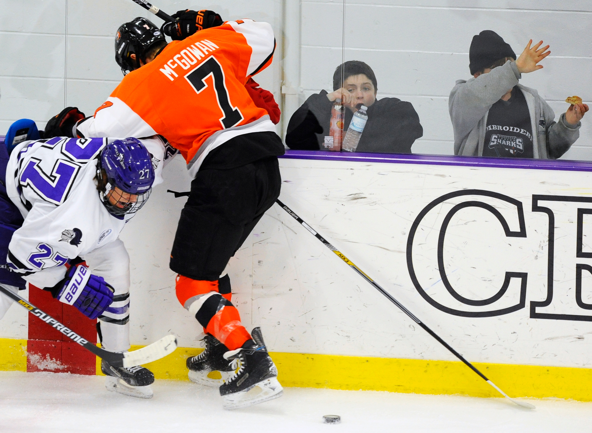 Holy Cross' Danny Lopez and RIT's Brad McGowan slam into the glass startling young fans on Friday, Feb. 13, 2015.