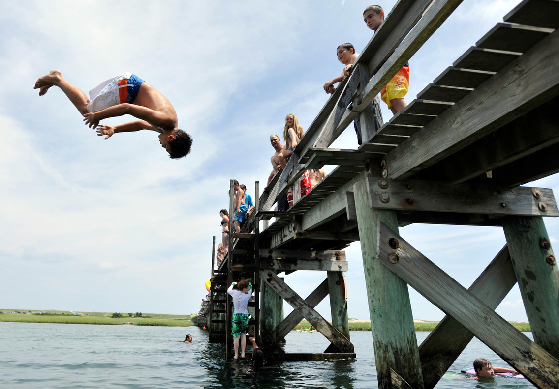 Carson Schemenaur, 11, of Sandwich back flips off of the Sandwich boardwalk at high tide.