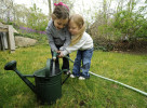 Sisters Lily, left, and Annabelle Giardino, 5 and 3, work together to fill their watering can for the bed of flowers they just planted with their father and grandmother on Mother's Day.