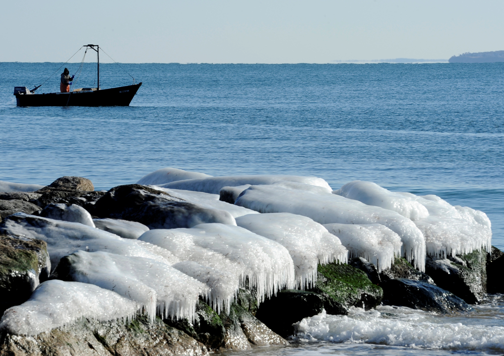 FALMOUTH -- 010914 -- A fisherman hauls up his catch near an ice-coated jetty off Surf Drive on Vineyard Sound.