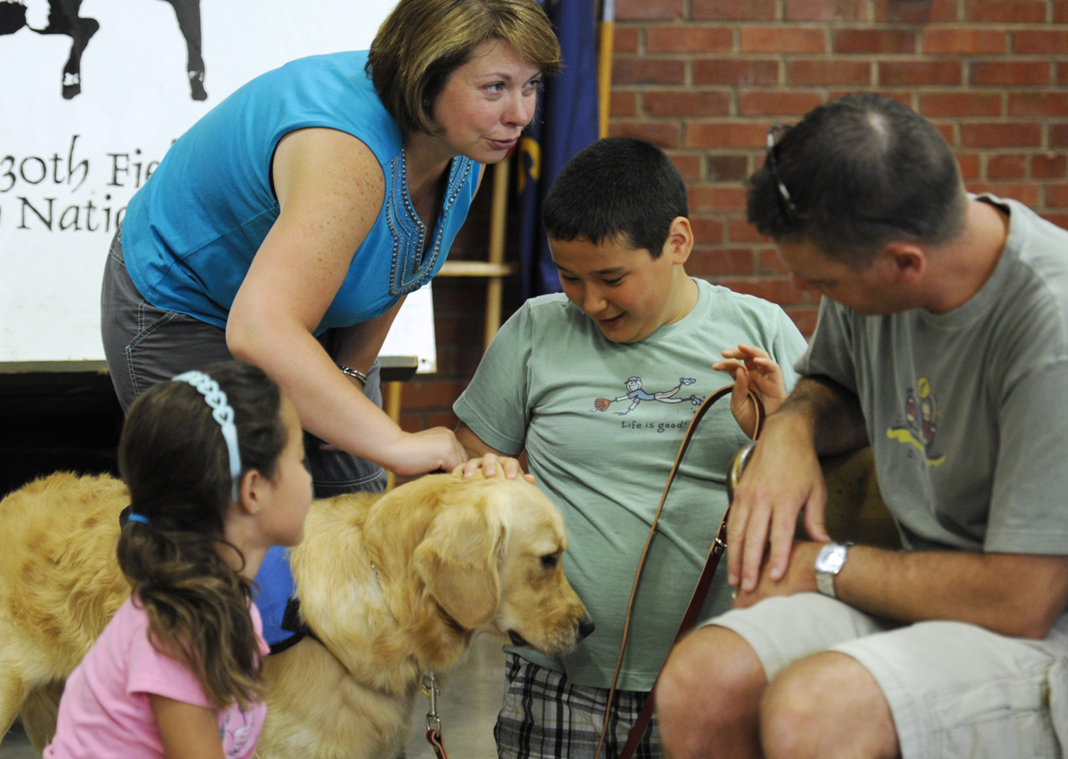 CONCORDIA, Kan. -- 06/20/11 -- Abby, Tina, Nickolas and PJ Qvarnstrom meet Nick's service dog, Keno, for the first time at the Kansas National Guard armory.