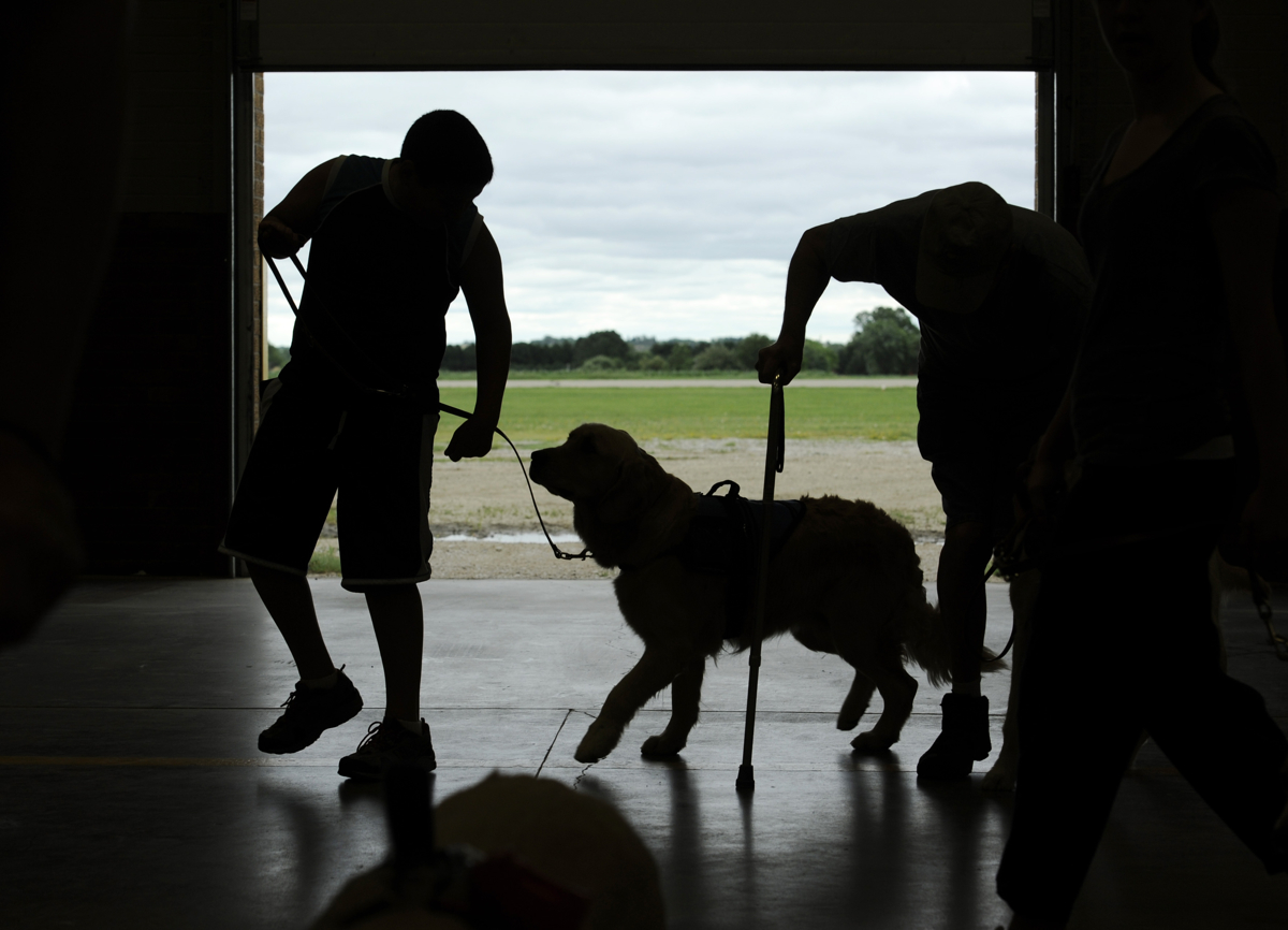 CONCORDIA, Kan. -- 06/21/11 -- Nickolas practices walking with Keno around the Kansas National Guard armory gymnasium with about 20 other new handlers and their dogs. Other clients receiving dogs ranged in their ages and disabilities. CARES clients, to date, have ranged in age from 5 to 92. One man receiving an Irish Setter was struck by lightning and as a result suffers from brain damage and sight loss. His dog will assist him with his mobility issues. There were two children with juvenile diabetes receiving medic alert dogs. These animals will learn the scent their owner's body chemistry and will notify them when their blood sugar is dangerously high or low.