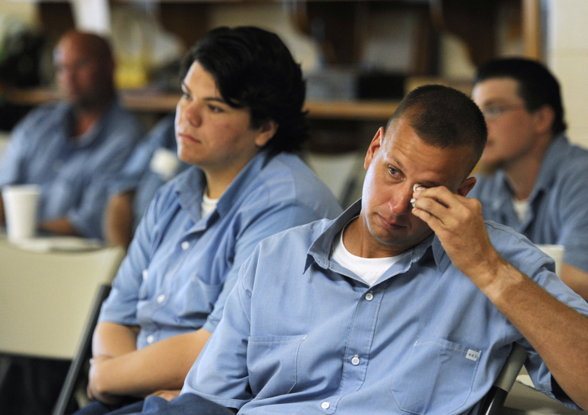 ELLSWORTH, Kan. -- 06/23/11 -- Ellsworth Correctional Facility inmate Craig Ivancic wipes away a tear as he listens to the visitors share the reasons why they are receiving the services dogs. Ivancic has trained over 55 dogs in his 5 and a half years in the dog training program. Ivancic says the inmates do get attached to the first couple dogs they train and sometimes find it hard to say goodbye but {quote}the good news is you know its going to help somebody.{quote} He added a personal note about how the program has helped him cope his offence, {quote}Through working with these dogs, it's my way of repaying everyone that I hurt.{quote}