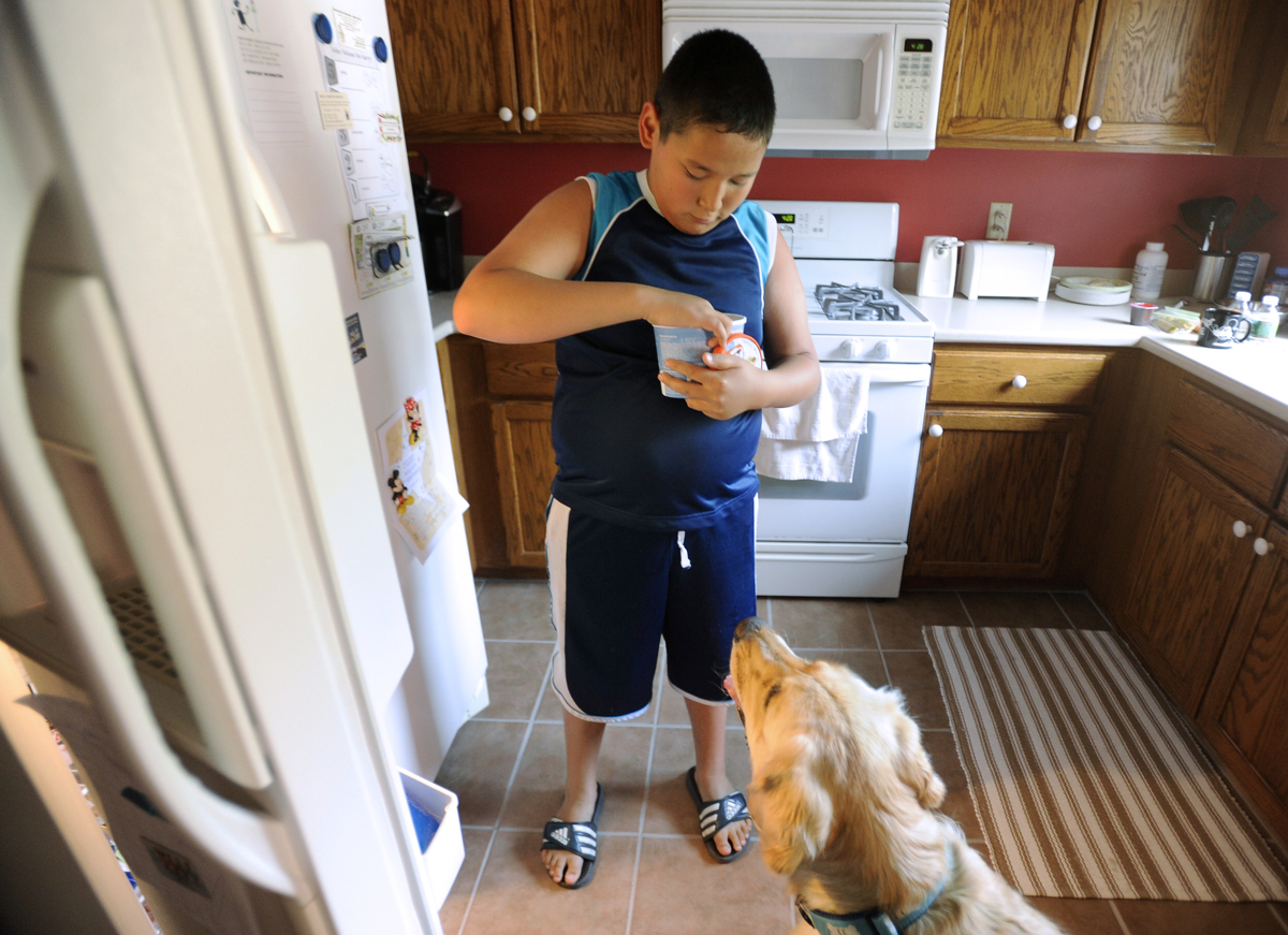 WEST YARMOUTH -- 071911 -- Back at home, Nickolas Qvarnstrom digs out a frosty pup treat to give to Keno after a walk in the hot weather.