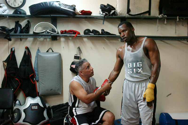 Coach Orlando Valles helps Maurice Cole take off his gloves after working the bag at Manfredo's Gym on Tuesday, July 3, 2007. Valles volunteers his time training 16 other young boxers, but says he gives special attention to Cole because of his talent and discipline.