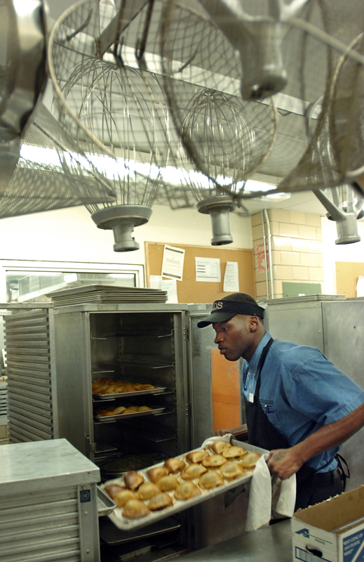 Maurice Cole pulls out a tray of calzones from the warmer just before the dinner rush at the Sharpe Refectory dining hall on the Brown University campus on Thursday, April 19, 2007.