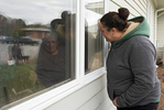YARMOUTH - Jessica Neal visits her mother, Susan, at Mayflower Place nursing center while a lilac bush for Earth Day is planted in front of her window. Susan lives with Alzheimer's disease and is accustomed to her daughter and husband visiting her for lunch everyday. Now that all visitors are restricted from assisted living facilities to limit resident's exposure to COVID-19, many family members have turned to window visits like this.