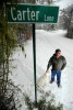 Brent McFarland and his dog, Angus, stand underneath the new Carter Lane sign leading to his home that was installed recently off of Jackbon Road.  McFarland's girlfriend choked on a marshmallow and died in the middle of the night when paramedics did not arrive at his residence in time to save her due to the unmarked road.
