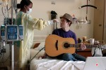 Emerson College student Matthew Starring, 23, takes a quick break from rehearsing his upcoming solo performance so personal care attendant Sherina Mayo can check his vital signs in his room on the 12th floor for oncology at Brigham and Women's Hospital on Friday, April 3, 2009. Matthew recently found out that his leukemia had relapsed for the second time after receiving a bone marrow transplant from his sister last summer and then being in remission for eight months.