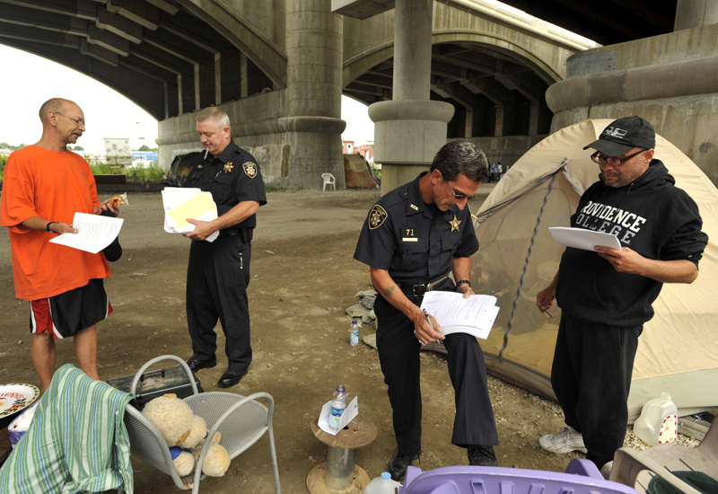Officers from the R.I. Sheriff's Department deliver hearing notices to Camp Runamuck residents Timothy Webb (far left) and Norman Trank (far right) on Thursday afternoon. Webb and Trank have been partners for 7 years. Webb is a cosmetologist and Trank is a master chef, both are now unemployed. {quote}This is only temporary.{quote} Webb said of the situation.