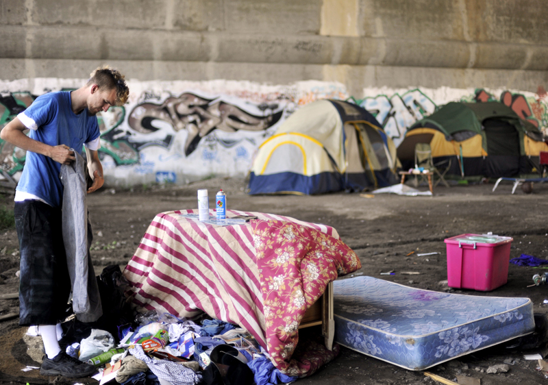 Luke Michaú'd, 19, folds a pair of pants from a pile of his belongings that he dumped out his tent the night before when he and his crew decided to start moving to their new site on Westminster Street earlier than planned.