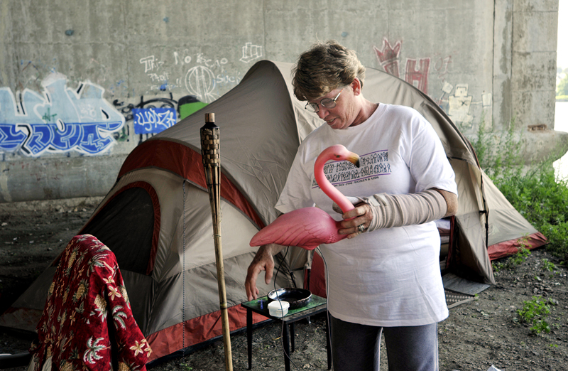 Barbara Kalil, 50, settles into her new space underneath the Washington Bridge in East Providence. {quote}I try to make things homey. Home is where ever you are.{quote} Kalil said while placing pink flamingo yard decorations outside the entrance to her tent.