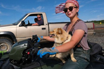 Johnna Bouker, from Dillingham, Alaska, rides a four-wheeler with her dog as her father, John Paul Bouker, looks on, in Ekuk, Alaska on July 4, 2019. 964 setnet permits were fished last year in Bristol Bay. Approximately 60 of those are fished on Ekuk, where fishing families set up seasonal camps.  (Photo by Karen Ducey)