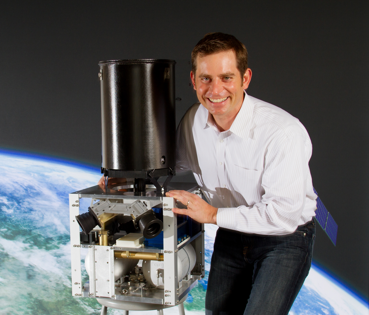 Jason Andrews, CEO of Andrews Space, is photographed next to a full scale model of their  SCOUT commercial imaging space craft. (© copyright Karen Ducey)