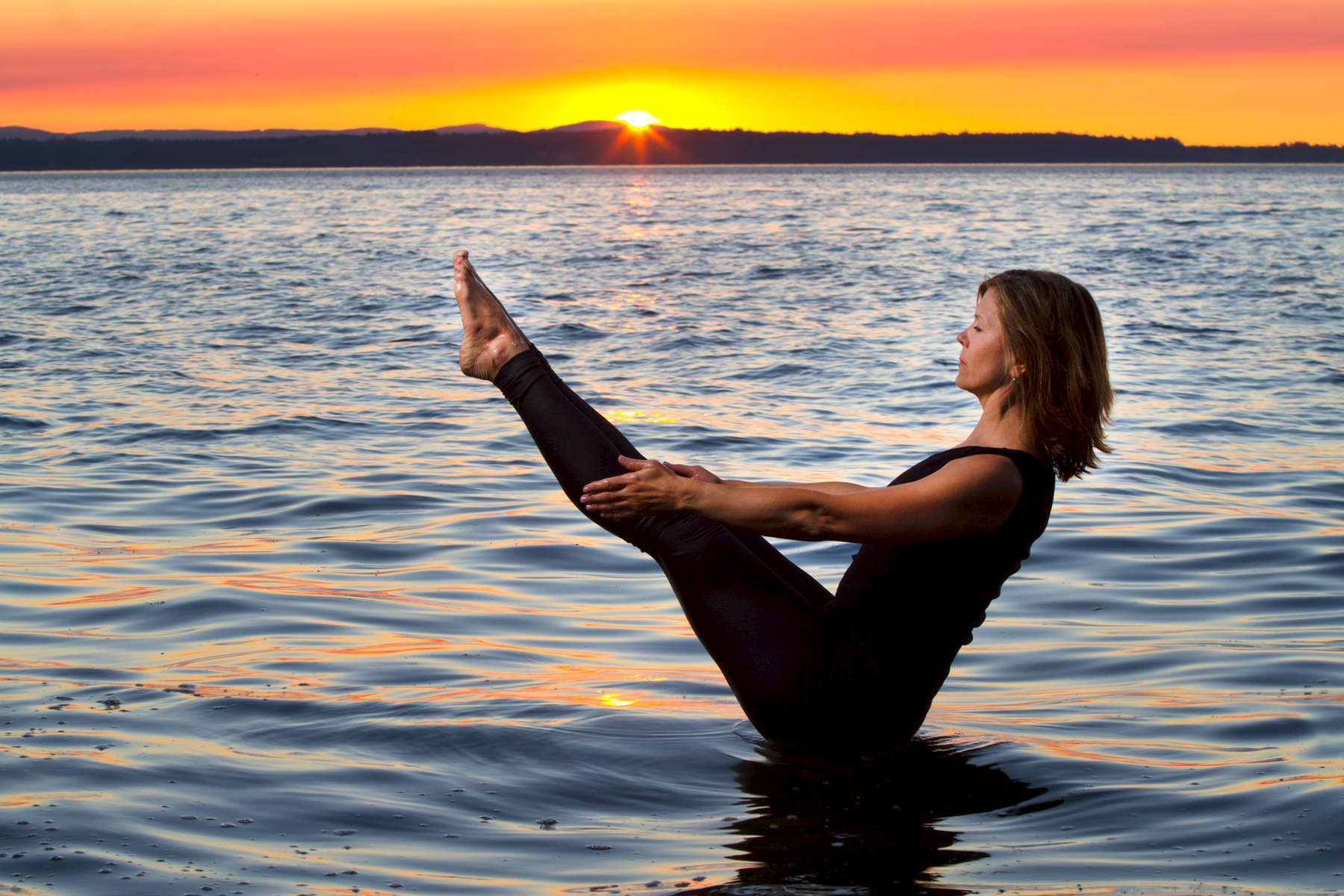 Angeline Johnston, yoga instructor and owner of Richmond Beach Yoga, poses at a beach in Edmonds, Wash. on July 31, 2015. (photo © Karen Ducey)