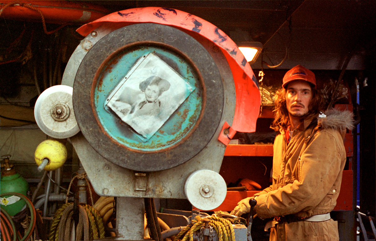 "Aboard the deck of the F/V Big Valley, crewmen Eric Grumpke runs the hydrolics next to the crab coiler which bears a picture of Barbara Stanwyck, star of the television show that is the boat's namesake, while the boat is in King Cove, Alaska preparing for the red king crab season on October 29, 1993. Grumpke drove the crane that shifted gear and equipment on deck. In the winter, arctic nights last 18 hours. The sun barely comes above the horizon before it begins its retreat back below the surface. Everyone's eyes adjust to the long winter nights, creating a glassy-eyed crew. The ""Aleutian stare"" is a common affliction everyone gets as a result of fatigue and being in this empty, gray world for indefinite periods of time. Heart failure killed Grumpke only 19 days after this picture was taken while he was operating the crane.  © copyright Karen Ducey"