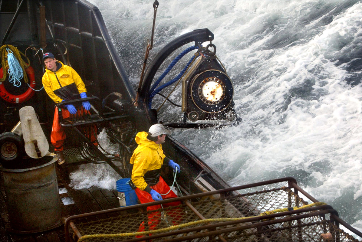 Crewman Lee Fleury prepares to throw the grappling hook at a crab pot buoy off in the distance while Lyndon Yockey (rear) runs the hydrolics to manuever heavy crab pots being stacked onboard. The 2003 Bristol Bay red king crab season lasted 5 days and 2 hours and was plagued with gale force winds of 35 knots or higher almost everyday causing to seas to rise 10 to 15 feet. © copyright Karen Ducey