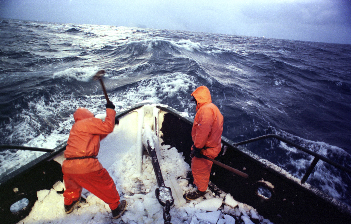 Heaving sledgehammers, two crew members begin a frigid January morning in 1995 by smashing a coat of frozen sea spray from the bow of the Polar Lady during opilio crab season in the Bering Sea. An iced-over boat can become dangerously top-heavy in rough seas and roll over. After four or so hours of sleep deckhands rise, beat ice off the boat with baseball bats and sledgehammers, and begin fishing. Crab fishing in the Bering Sea is considered to be one of the most dangerous jobs in the world. This fishery is managed by the Alaska Department of Fish and Game and is a sustainable fishery. The Discovery Channel produced a TV series called {quote}The Deadliest Catch{quote} which popularized this fishery. Today this fishery, largely based out of Dutch Harbor, AK has been consolidated resulting in a lot less boats fishing. © copyright Karen Ducey