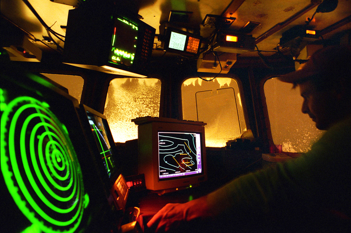 Assistant skipper Jeff Morehouse guides the fishing vessel {quote}Polar Lady{quote} through a stormy night using GPS, radar, sideband radio, depth finders, and other electronic equipment in the wheelhouse during an opilio crab season in the Bering Sea in January 1995. Nights are long and cold in the arctic in the winter. Crab fishing in the Bering Sea is considered to be one of the most dangerous jobs in the world. This fishery is managed by the Alaska Department of Fish and Game and is a sustainable fishery. The Discovery Channel produced a TV series called {quote}The Deadliest Catch{quote} which popularized this fishery. Today this fishery, largely based out of Dutch Harbor, AK has been consolidated resulting in a lot less boats fishing. © copyright Karen Ducey